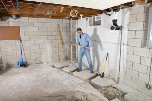 man in basement removing cement floor